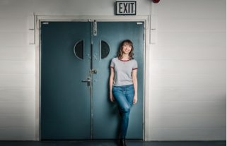 Izzy standing in front of a  theatre door