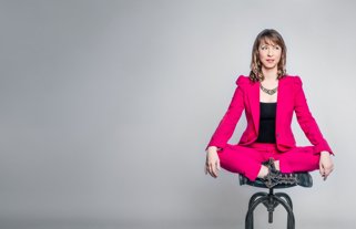 Izzy sitting on a stool in a pink suit